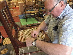 student working on laced cane chair